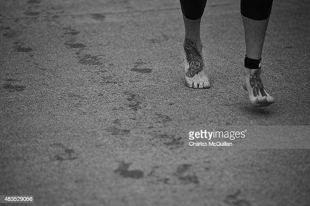 A female Competitor sports a tiger tattoo on her foot as she makes transitional stage from swim to bike during the Ironman triathlon event on August...