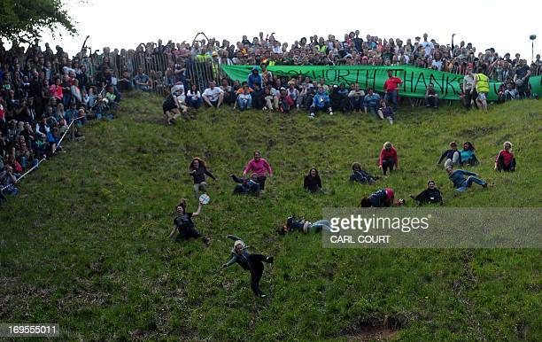 Female competitors run down Coopers Hill in pursuit of a fake foam round Double Gloucester cheese during the annual cheese rolling and wake near the...