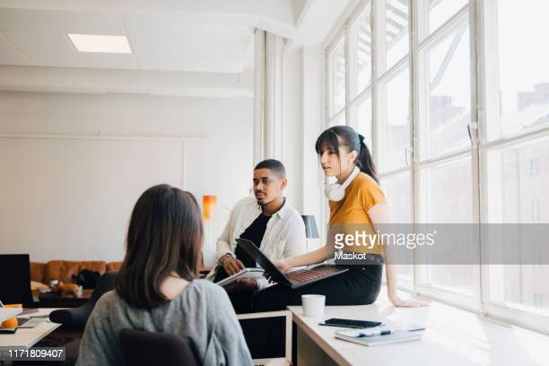 female computer engineer discussing with colleagues while sitting on desk in office - vanguardians stock pictures, royalty-free photos & images