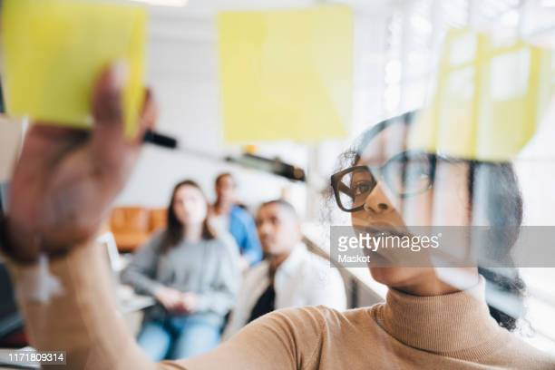 female computer hacker sticking adhesive notes on glass with colleagues sitting in background - strategy stock pictures, royalty-free photos & images