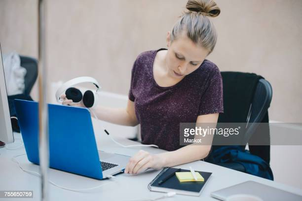 Female computer programmer connecting headphones to laptop at desk in office