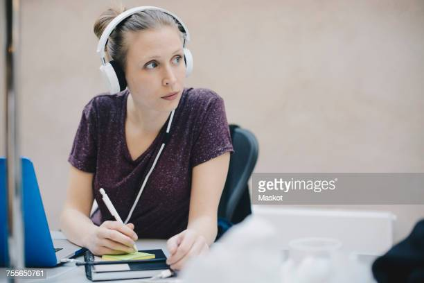 Female computer programmer looking away while writing on adhesive note in office