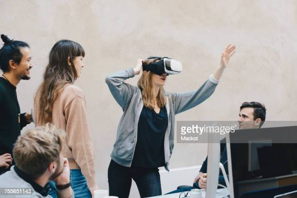 Female computer programmer using VR glasses while standing with colleagues in office