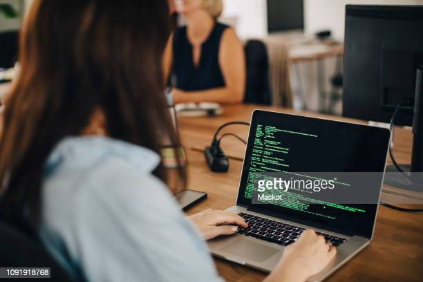 female computer programmer working at desk in creative office - coding stock pictures, royalty-free photos & images