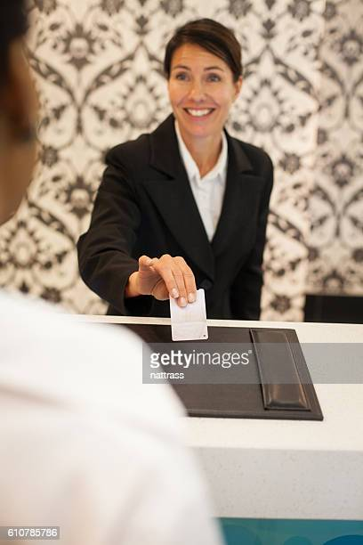 Female concierge handing room key to guest