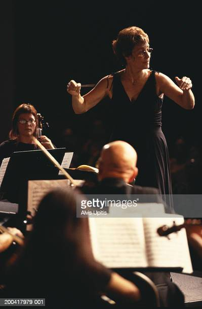 Female conductor performing with orchestra (focus on woman)
