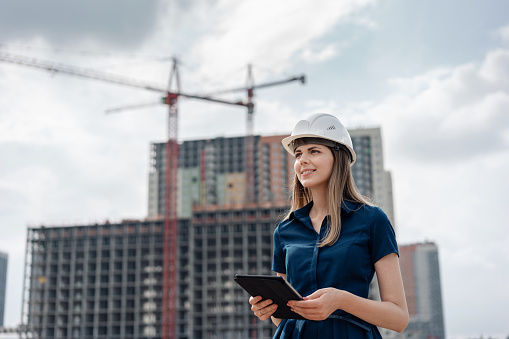 Female construction engineer. Architect with a tablet computer at a construction site. Young Woman looking, building site place on background. Construction concept 1005008594