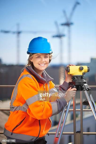 Hembra sitio de construcción surveyor mirando a la cámara