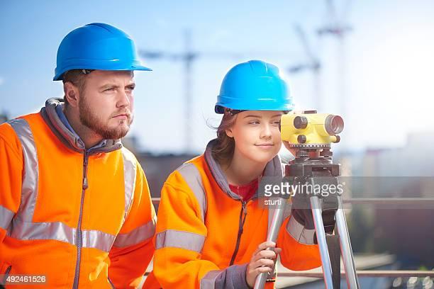 female construction site surveyor supervisor using Theodolite