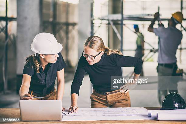 Female construction worker consulting an architect