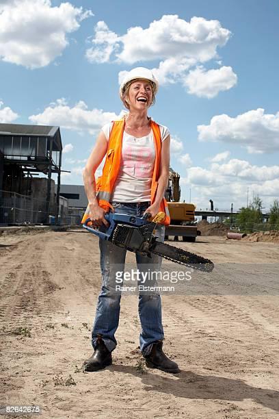 Weibliche Bauarbeiter holding Kettensäge