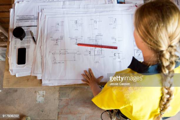 a female construction worker looks at site plans - building contractor stock pictures, royalty-free photos & images