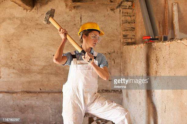 A female construction worker swinging a sledgehammer