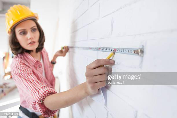 Female construction worker using a tape measure