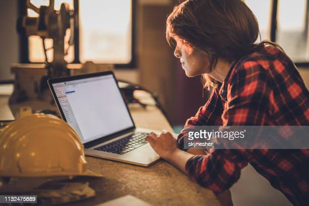 bauarbeiterinnen, die laptop bei der renovierung des hauses benutzen. - handwerker stock-fotos und bilder