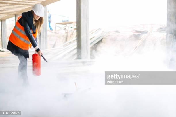 trabalhador da construção fêmea com um extintor de incêndio no canteiro de obras - extintor de incêndio - fotografias e filmes do acervo