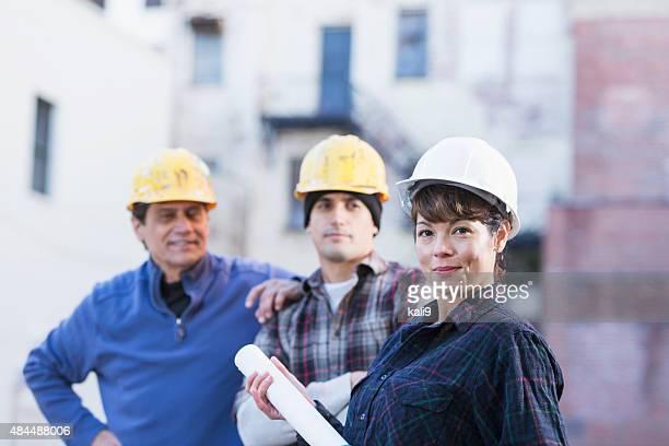 Weibliche Bau Arbeiter mit Gruppe von Männern