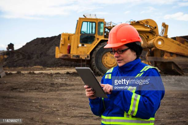 female construction worker with tablet computer on construction site - powerofforever stock pictures, royalty-free photos & images