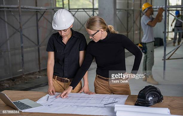 Female Constructor And Architect Reviewing Blueprints
