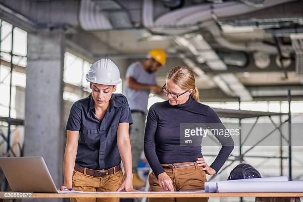 Female constructor and female architect reviewing blueprints