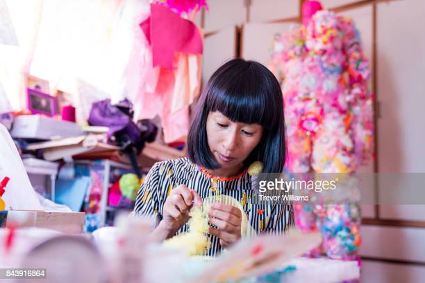 A female contemporary artist working in her studio creating art with textiles