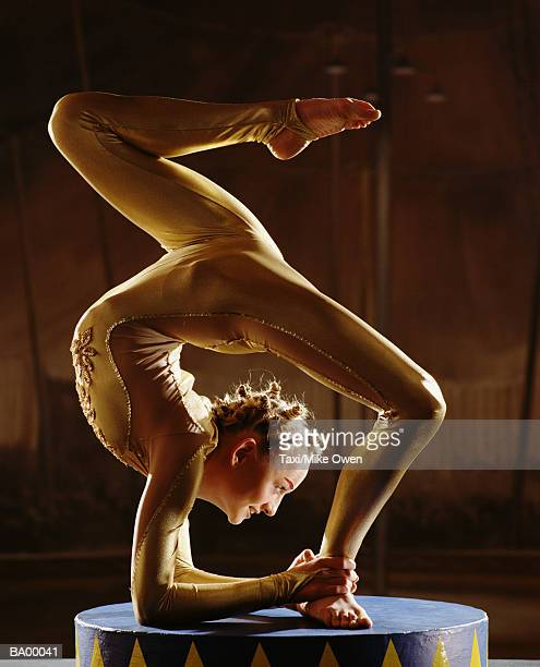 Female contortionist bending over backwards, profile