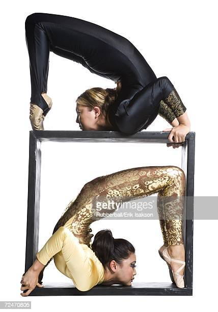 female contortionist duo with box prop - contortionist stock photos and pictures