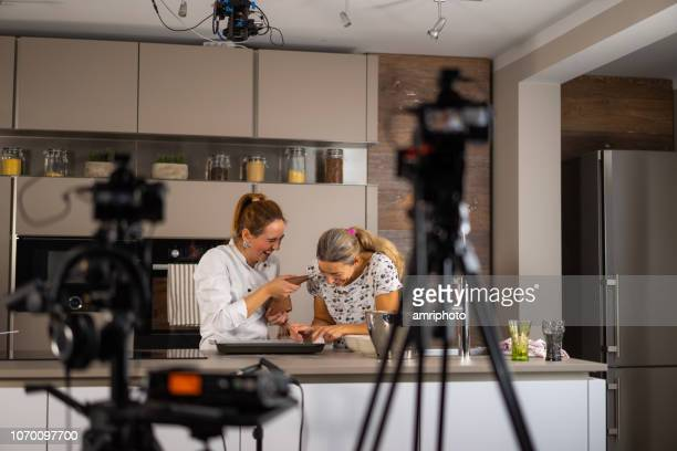 female cook and film making assistant having fun on set in kitchen - film set stock pictures, royalty-free photos & images