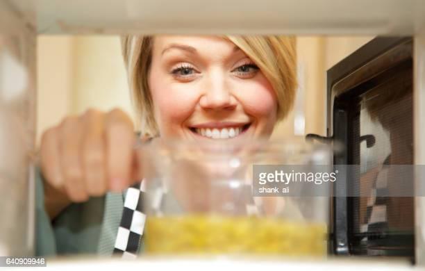 female cook heating food in microwave
