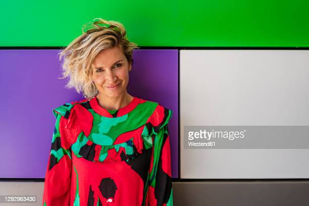 female cook in casual standing against colorful wall - southern european descent stock pictures, royalty-free photos & images