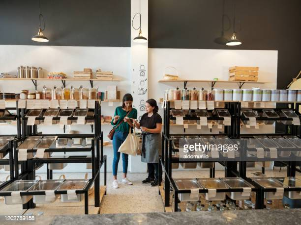 Female costumer and shop assitant looking at products in store