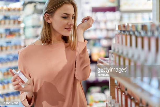 female costumer is buying perfume at a store - perfume stock pictures, royalty-free photos & images