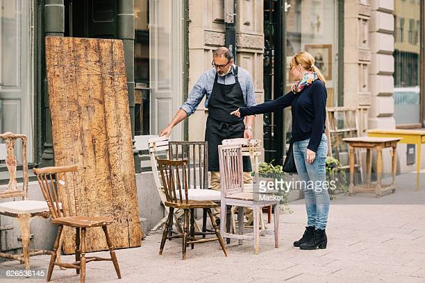Female costumer pointing while retailer looking at chair outside antique shop