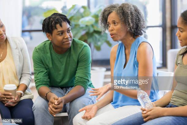 Female counselor advises people during support group meeting
