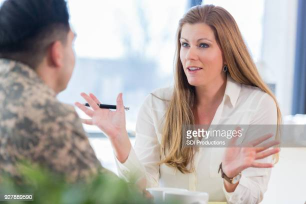 female counselor talks with military veteran - veterans stock photos and pictures
