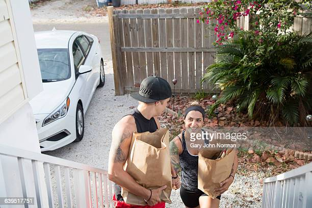 Female couple carrying groceries home