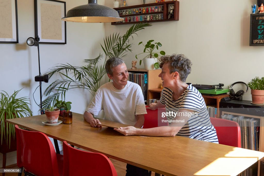 Female couple discussing finances together in their dining room : Stock-Foto
