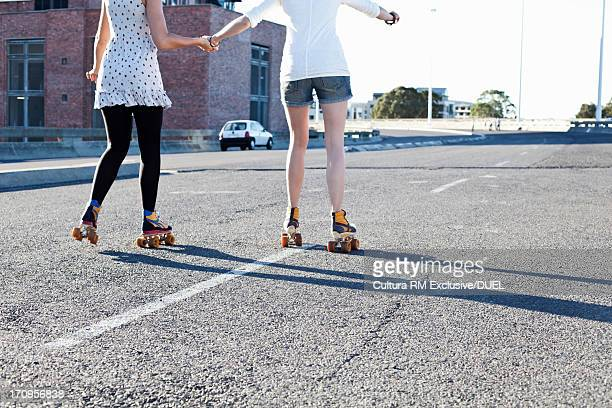Female couple holding hands rollerblading