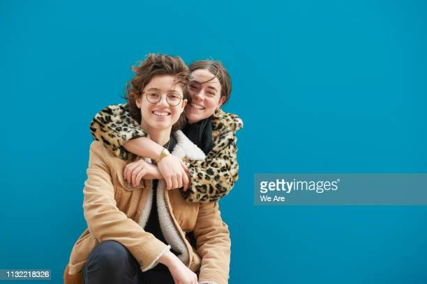 female couple in an embrace. - colour block stock pictures, royalty-free photos & images