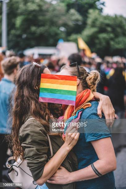 female couple kissing behind a rainbow flag - lgbtqi pride event stock pictures, royalty-free photos & images