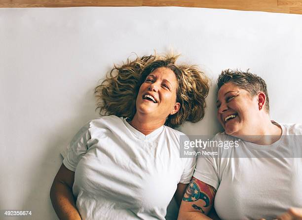 female couple laughing together - androgynous stock pictures, royalty-free photos & images