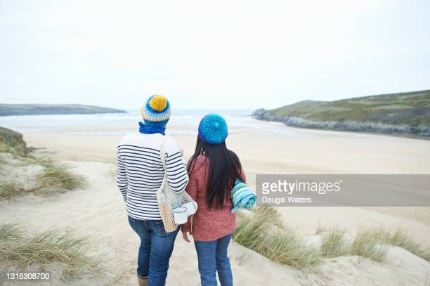 female couple looking out to sea from beach. - headwear stock pictures, royalty-free photos & images