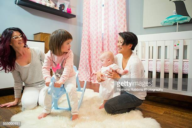 Female couple playing on floor with baby and toddler daughters