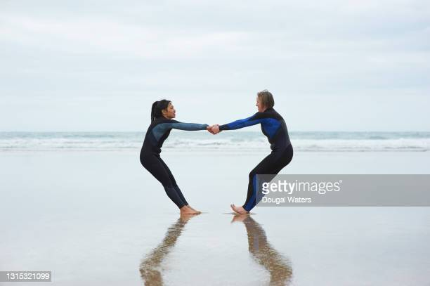 female couple preparing for sea swimming. - sea stock pictures, royalty-free photos & images