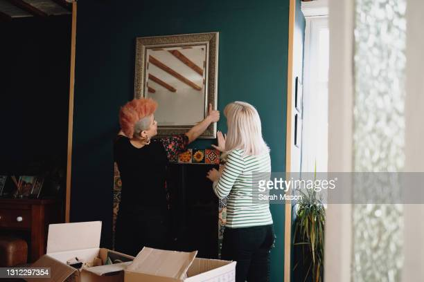 female couple putting up mirror on wall - gender identity stock pictures, royalty-free photos & images