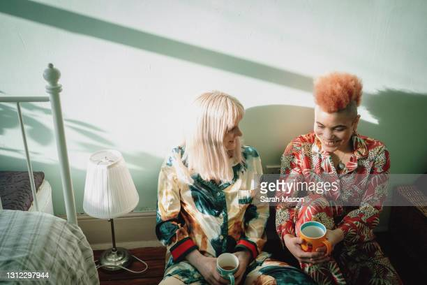 female couple sat on floor in pyjamas - pyjamas stock pictures, royalty-free photos & images