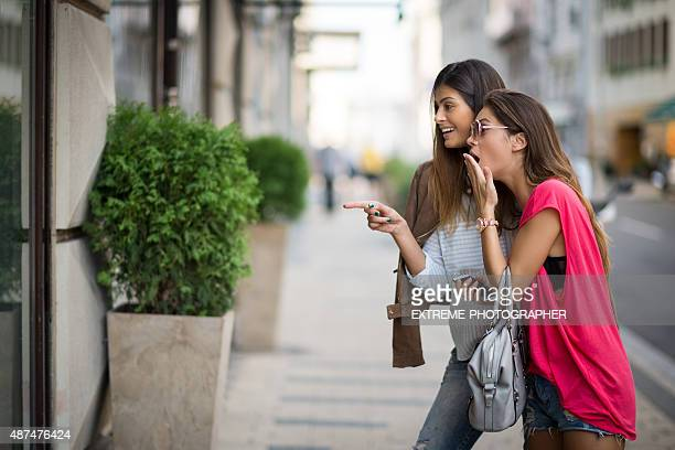 Female couple shocked at store window