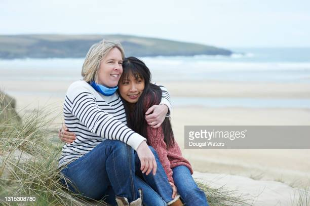 female couple sitting at beach and embracing. - dougal waters stock pictures, royalty-free photos & images