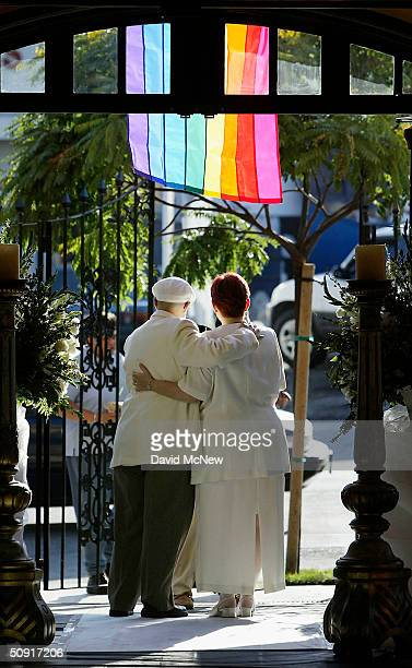 A female couple stands under a rainbow flag prior to the start of a symbolic mass gay wedding celebrated by more than 100 samesex couples on June 1...