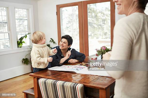 Female couple & their daughter draw in dining room